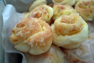 Mini rolls made of potato flour and topped with cheese, butter, and sugar